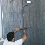 Loodgieter die de regendouche installeert